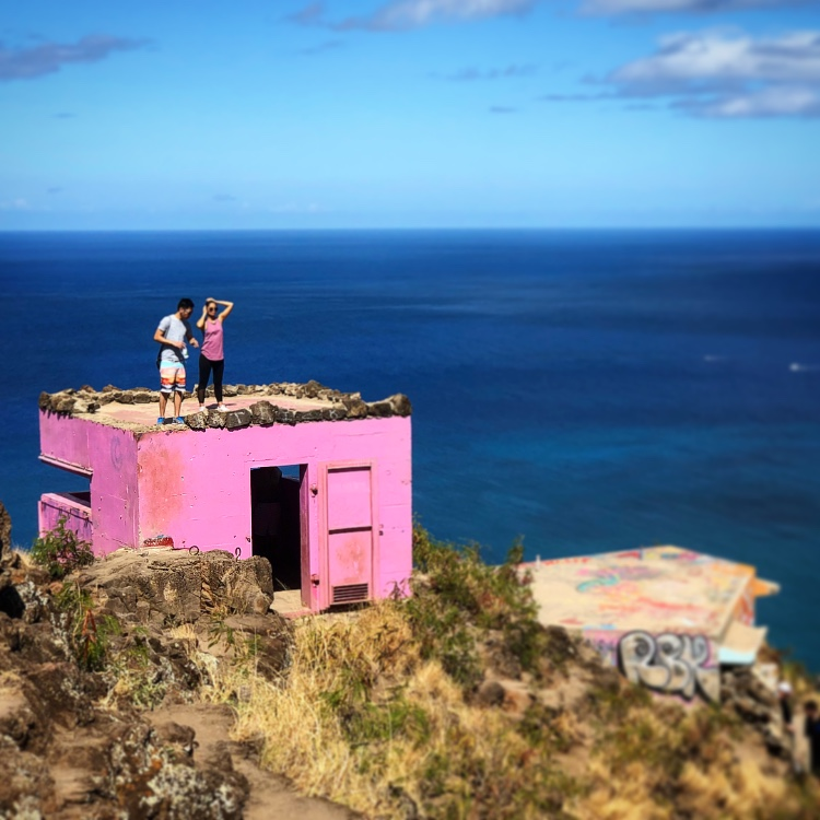 couple on top of bright pink pillbox with ocean background Maili pillbox