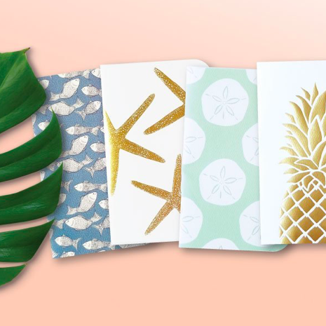 four island-inspired notebooks against pale pink background Hawaii artists