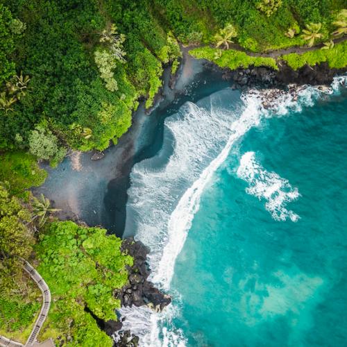 aerial view of black sand beach at Waianapapa State Park Maui vs. Kauai