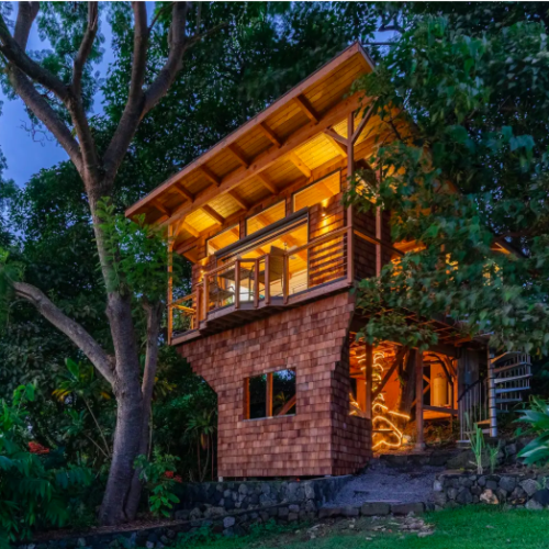 two story wood panels treehouse in Hawaii at night