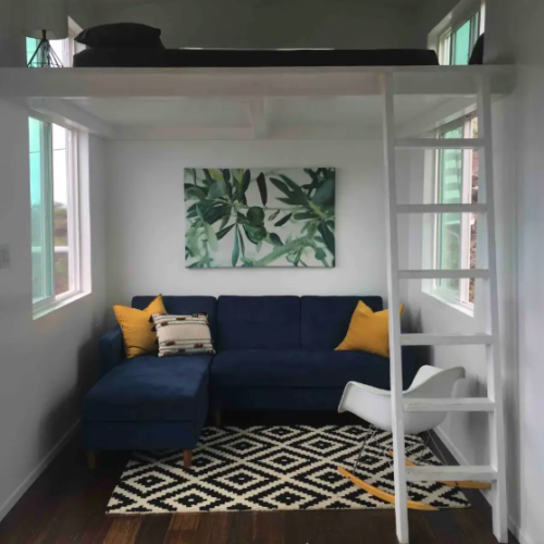clean tiny house with large blue couch and yellow pillows