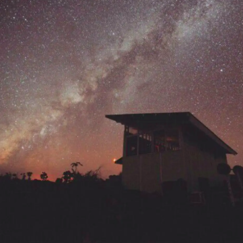 Milky Way galaxy behind wooden tiny house Airbnbs in Hawaii