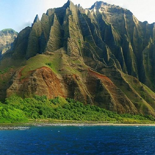 green mountain range on ocean with deep crevices Uber in Hawaii