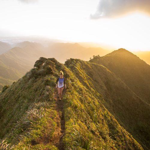 girl hiking mountain ridge during golden hour