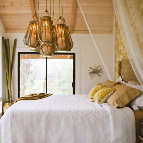 cozy, luxury bed with golden lights and pillows treehouses in Hawaii