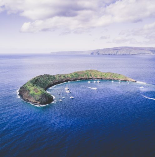 green crescent-shaped island surrounded by small white snorkeling boats things to do on Maui