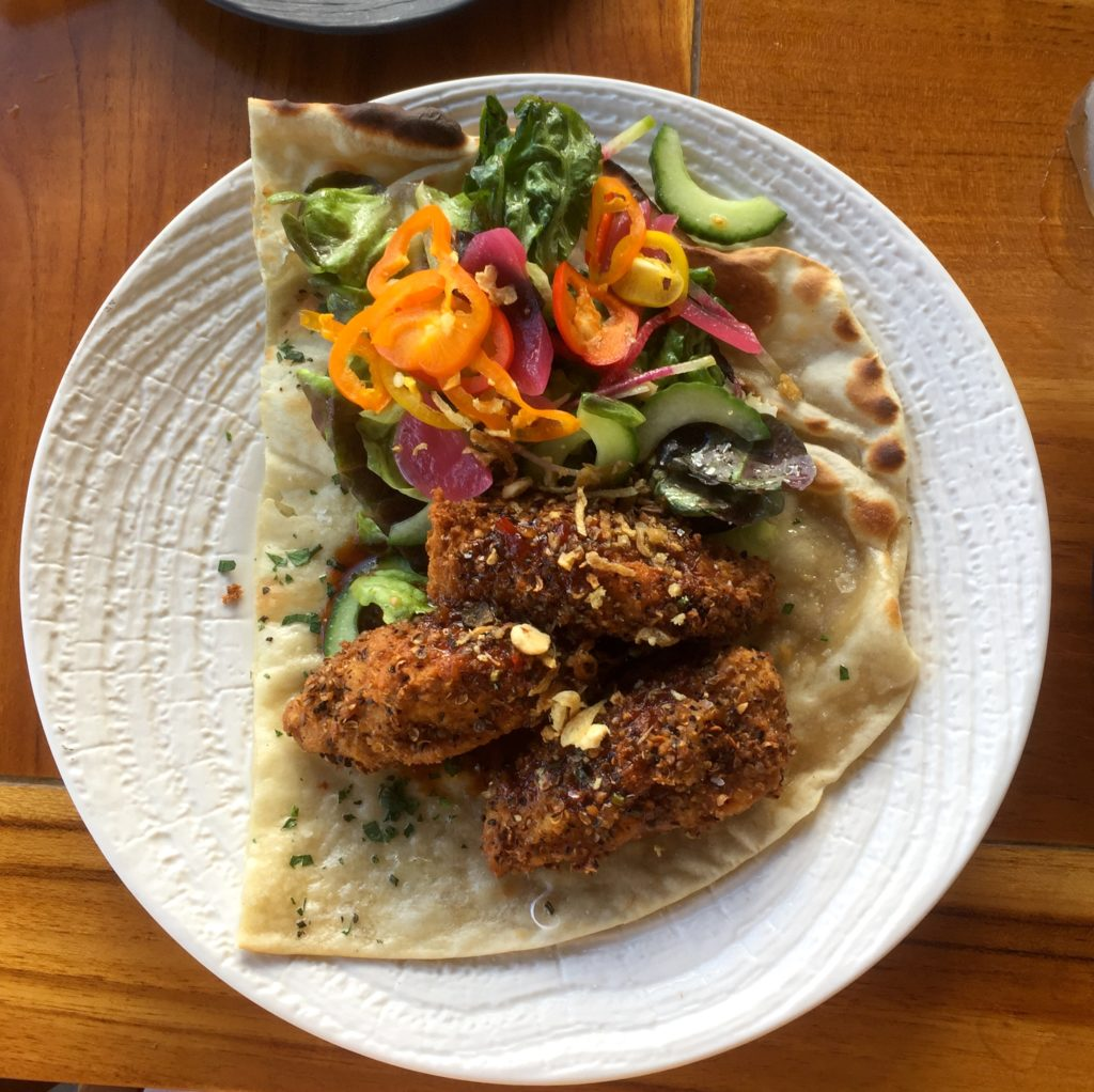 Ko Olina restaurants opener plate with lafa, a wrap with breaded chicken and colorful pickled vegetables