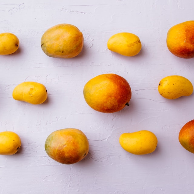 two types of mangoes arranged on white surface