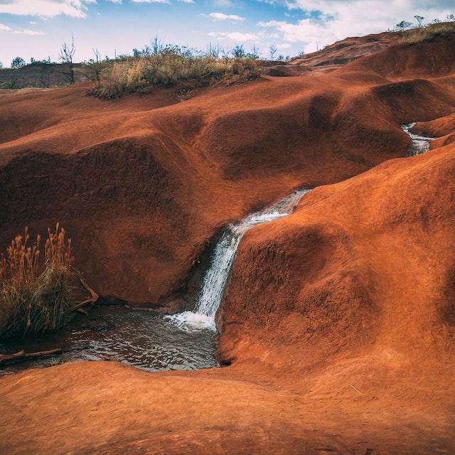 waterfall flowing through red dirt Kauai waterfalls