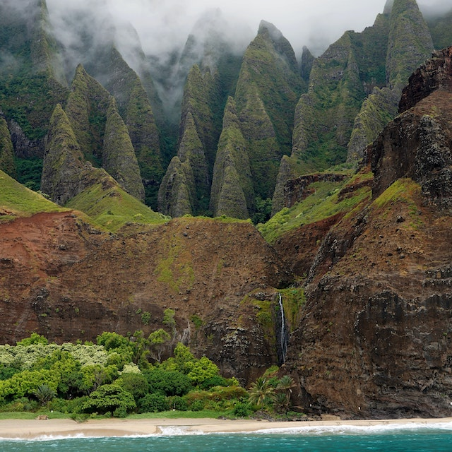 dwarfed waterfall in front of deep crevices of Na Pali Coast Kauai waterfalls