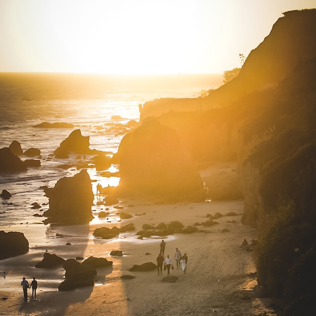 people walking between rock formations along beach during golden hour things to do in Malibu