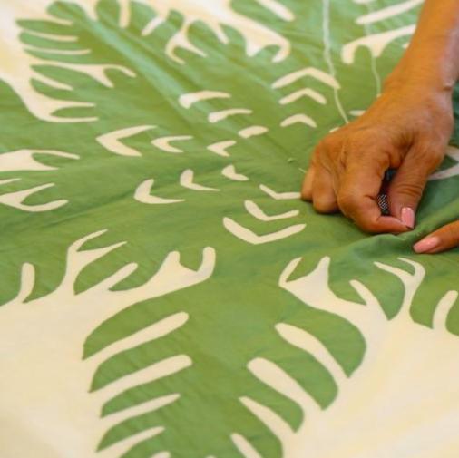 woman hand stitching green design onto quilt Hawaiian home decor