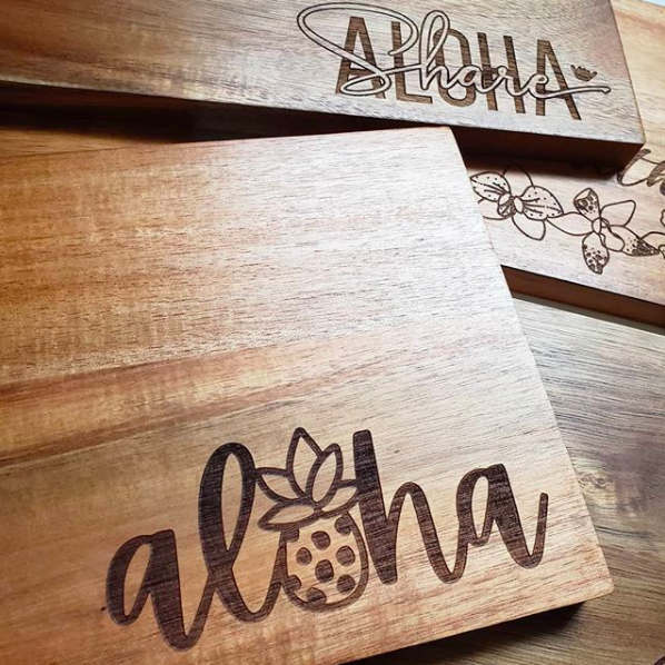 pile of dark wooden cutting boards with various Hawaii-themed prints and sayings