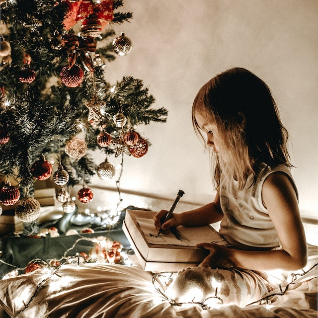 girl drawing a picture by a Christmas tree