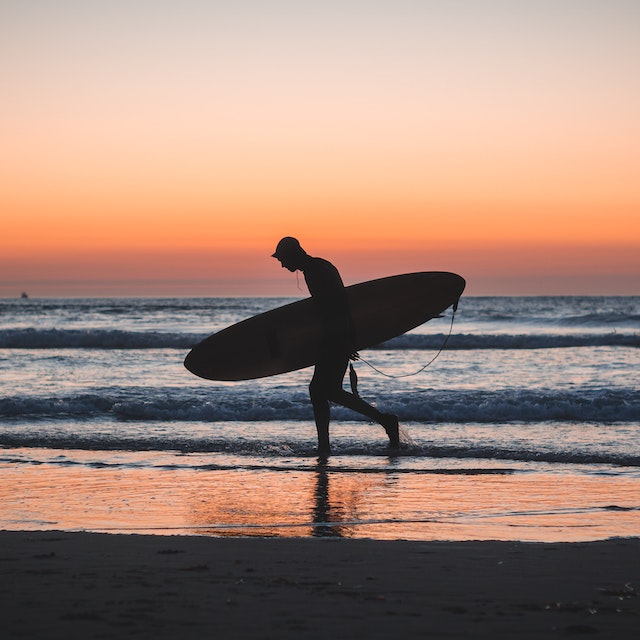 surfer walking along beach at sunrise in San Diego Warm Winter Vacations in the USA
