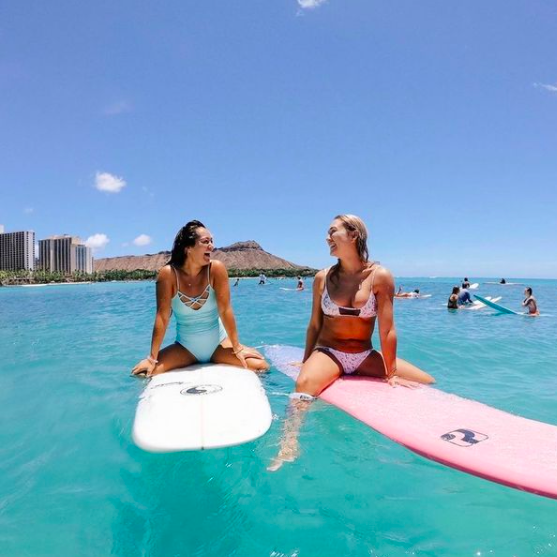 two women, one in blue one piece and one in white bikini, surfing by Diamond Head in Waikiki, Hawaii