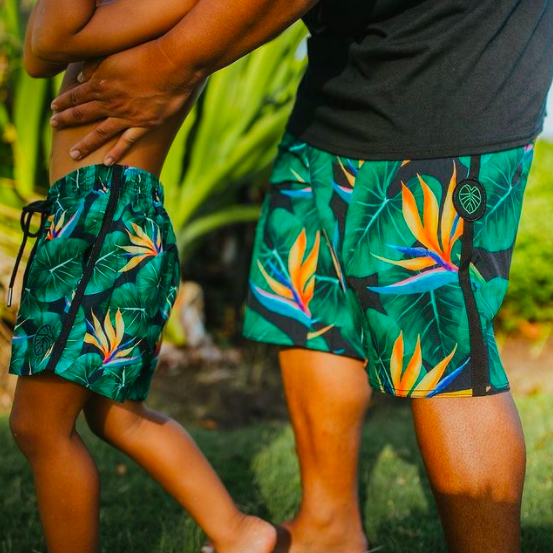 father and son in matching bird of paradise boardshorts Hawaii swimwear
