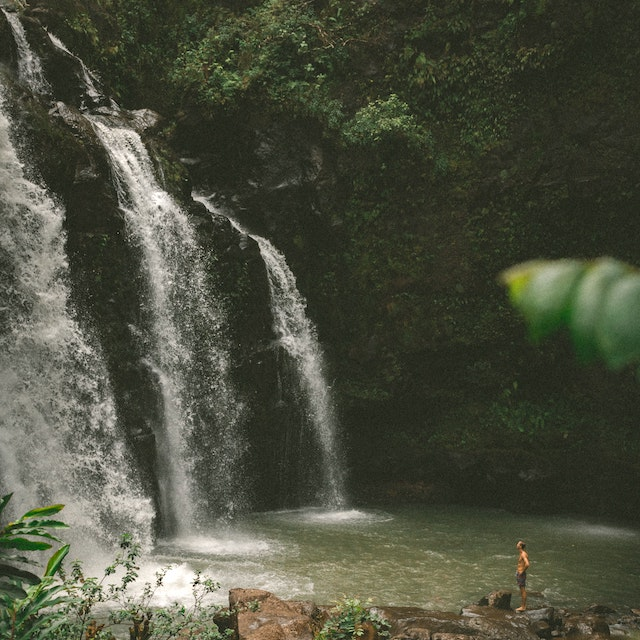 Upper Waikani Falls with person next to it