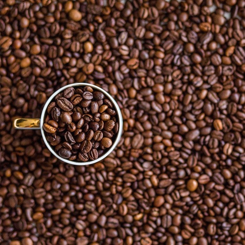 coffee beans in and around a coffee cup