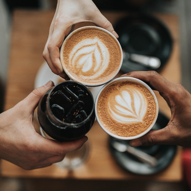three people cheers-ing coffee drinks the best Hawaii coffee companies